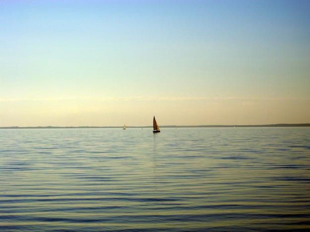 Iate navega no mar ao pôr do sol