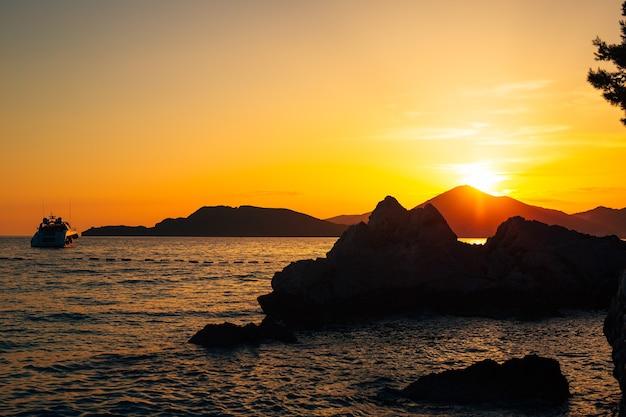 Iate no mar ao pôr do sol silhueta de um iate no backgro