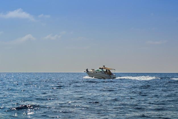 Iate no mar com pessoas na costa de budva ao pôr do sol