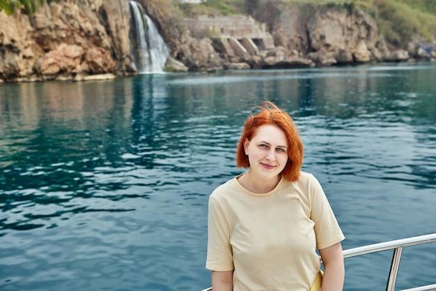 Iate turístico passa por uma pequena cachoeira, jovem mulher europeia posa para foto
