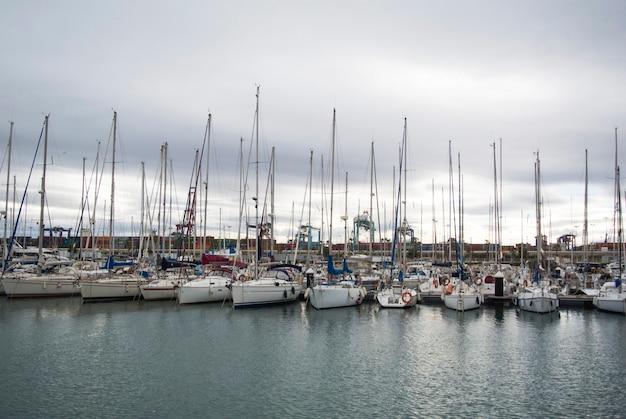 Iates e barcos de luxo no porto de valência no mar mediterrâneo. reflexão na água. iates brancos estão no porto espanhol de valência no início da primavera. céu nublado.