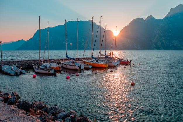 Iates no cais durante o pôr do sol no lago de garda. pôr do sol na riva del garda. o sol se põe nas montanhas. lago no norte da itália.