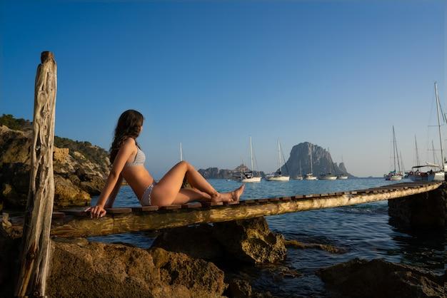 Ibiza cala d hort menina do pôr do sol do cais es vedra