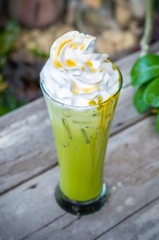 Ice matcha chá verde com chantilly na mesa de madeira