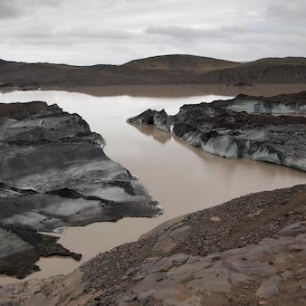 Iceberg sujos empoeirados na costa do lago glacial