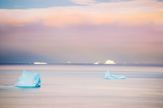 Icebergs azuis no oceano atlântico ao pôr do sol, oeste da groenlândia