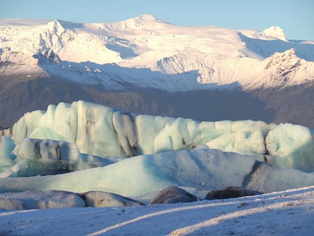 Icebergs enormes flutuando contra a montanha coberta de neve