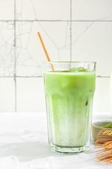 Iced matcha latte, chá verde com leite de amêndoa, ferramentas tradicionais de matcha, com palha de bambu em vidro na superfície branca