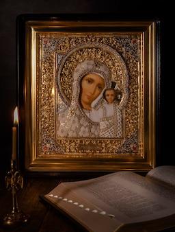 Ícone da mãe de deus de kazan com uma vela acesa da igreja ao lado