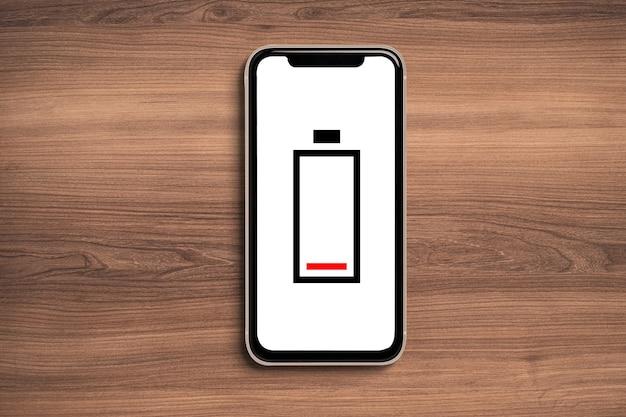 Ícone de bateria fraca simulado no smartphone em fundo de madeira.