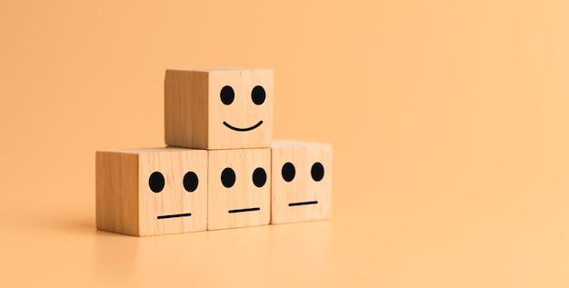 Ícone de cara feliz e triste no cubo de madeira na mesa. conceitos de avaliação do atendimento ao cliente e índice de satisfação.