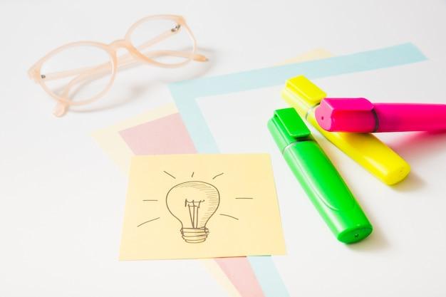 Ícone de ideia na nota adesiva com marcador de destaque; óculos e papéis de cartão