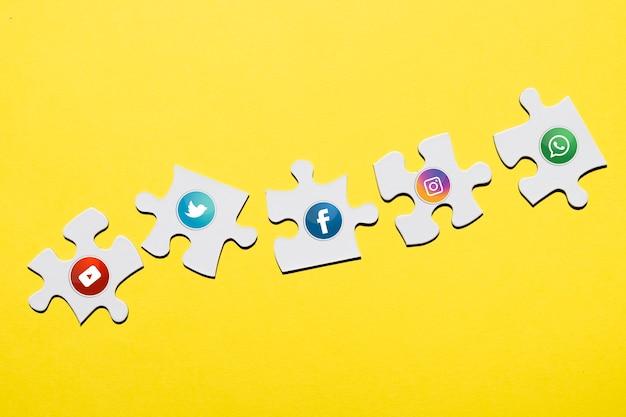 Ícone de mídia social na peça do quebra-cabeça branca sobre pano de fundo amarelo