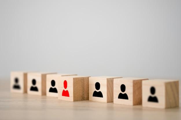 Ícone humano vermelho em um cubo de madeira na frente de outros cubos de madeira do ícone humano preto. liderança e conceito de pensamento diferente.