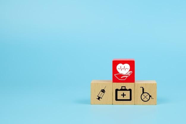 Ícone médico no cubo de blocos de brinquedo de madeira empilhados em forma de pirâmide