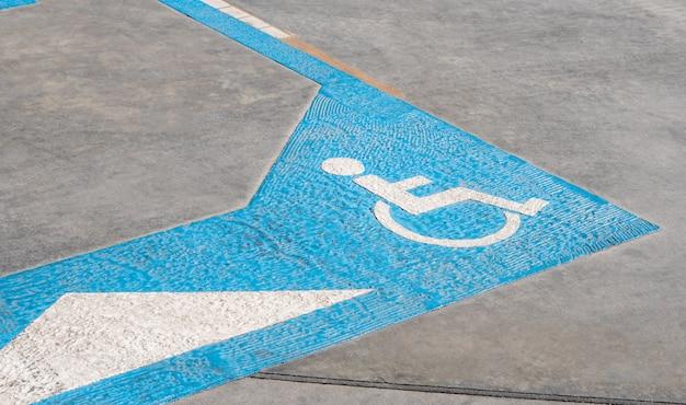 Ícone para deficientes no chão da reserva de área de estacionamento para pessoas com deficiência no posto de gasolina urbano