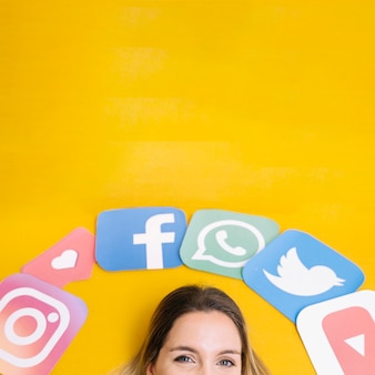 Ícones de aplicativos de mídia social sobre a cabeça da mulher em pano de fundo amarelo