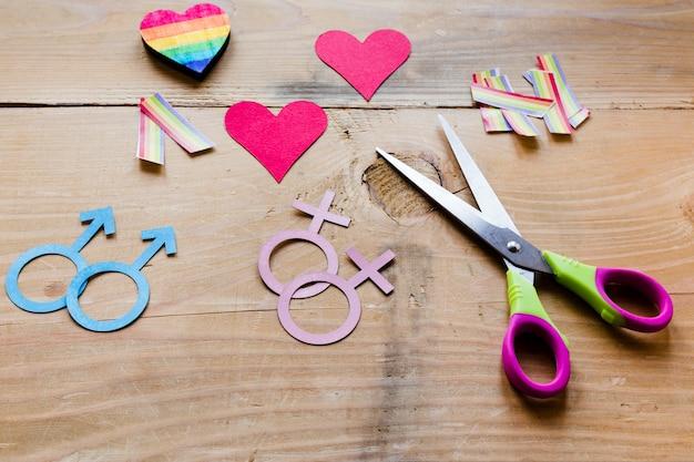 Ícones de casais homossexuais com corações vermelhos e arco-íris