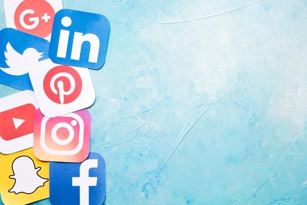 Ícones de diferentes mídias sociais na parede pintada de azul