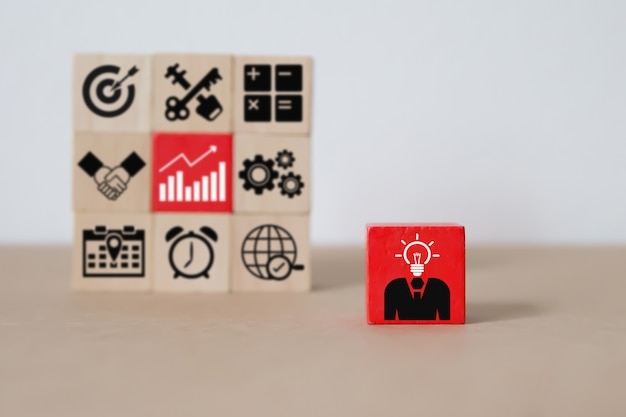Ícones de liderança e negócios em blocos de madeira.