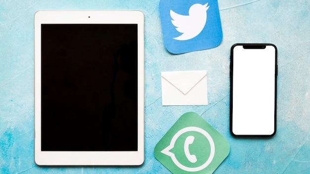 Ícones de mídia social com celular e tablet digital sobre fundo azul textura pintada