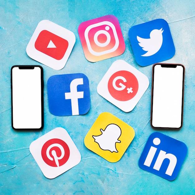 Ícones de mídia social com dois celular em branco na parede pintada de azul
