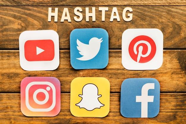 Ícones de mídia social perto de hashtag palavra sobre a mesa de madeira