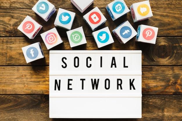 Ícones de rede conhecidos perto de texto de rede social sobre a mesa de madeira