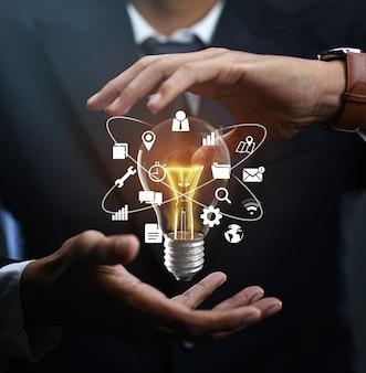 Ícones de tecnologia lâmpada incandescente flutuando na mão do empresário.