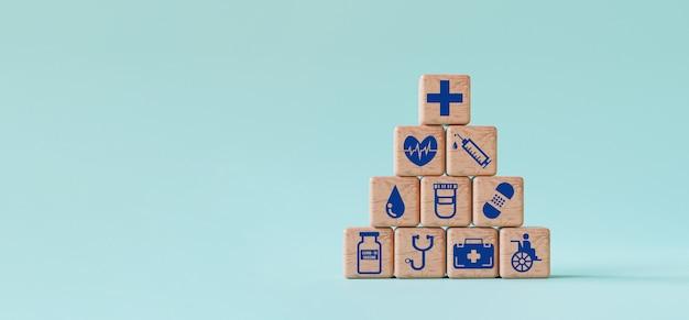 Ícones médicos e de saúde imprimem a tela em um bloco de cubos de madeira sobre fundo azul e copiam o espaço por renderização 3d.