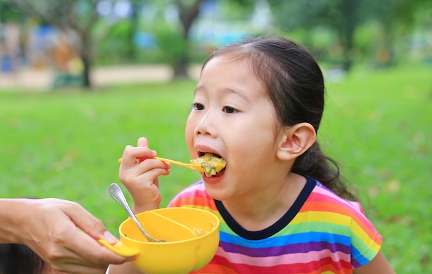 Idade asiática pequena da menina da criança do close-up aproximadamente 4 anos que comem o arroz pelo auto no jardim exterior.