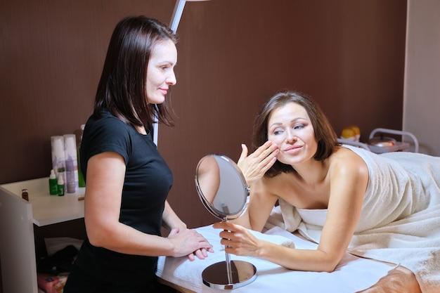 Idade, beleza, rosto, conceito de tratamento. mulher de meia-idade em consultório de cosmetologia, mulher feliz olhando no espelho de cosmetologia