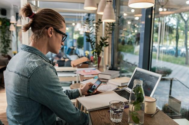Idade digital. jovem inteligente sentado em frente ao laptop, segurando um smartphone nas mãos