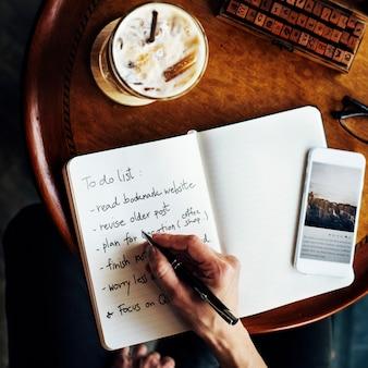Ideia aérea do close up da mão que escreve para fazer a lista no café
