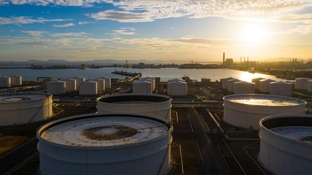 Ideia aérea do terminal do tanque com lotes do tanque de armazenamento do óleo e do tanque de armazenamento petroquimico no por do sol, opinião aérea do armazenamento industrial do tanque.