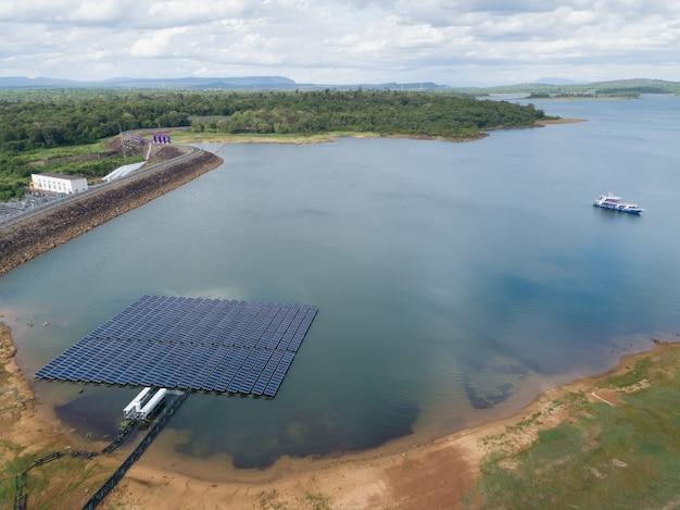 Ideia aérea dos painéis de flutuação da energia solar em um lago com vista natural verde - exploração agrícola das energias solares.