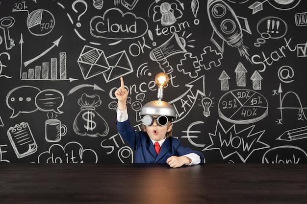 Ideia brilhante! aluno de criança engraçada em classe contra o quadro negro. criança feliz finge ser empresário. educação online e conceito de e-learning. de volta à escola