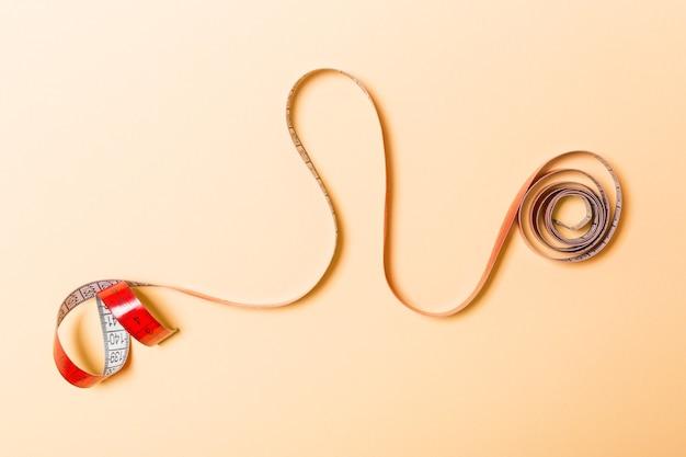 Idéia criativa de fita métrica espiral em fundo laranja. conceito de costura.