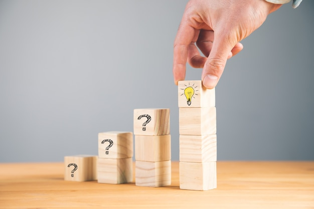 Ideia criativa do conceito e inovação. bloco de cubo de madeira na mão com símbolo