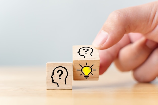 Idéia criativa do conceito e inovação. virar a mão sobre o bloco do cubo de madeira com cabeça símbolo humano e ícone de lâmpada