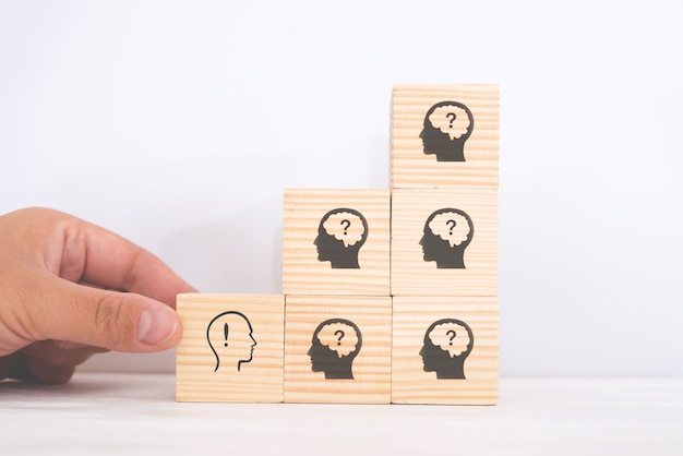 Ideia criativa e conceito de inovação. bloco de cubos de madeira selecionado à mão com o símbolo de uma cabeça humana e o ícone de ponto de exclamação