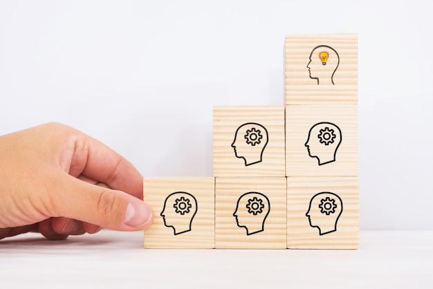 Ideia criativa e conceito de inovação. vista superior do bloco de cubos de madeira em pirâmide com o símbolo de uma cabeça humana e o ícone de lâmpada