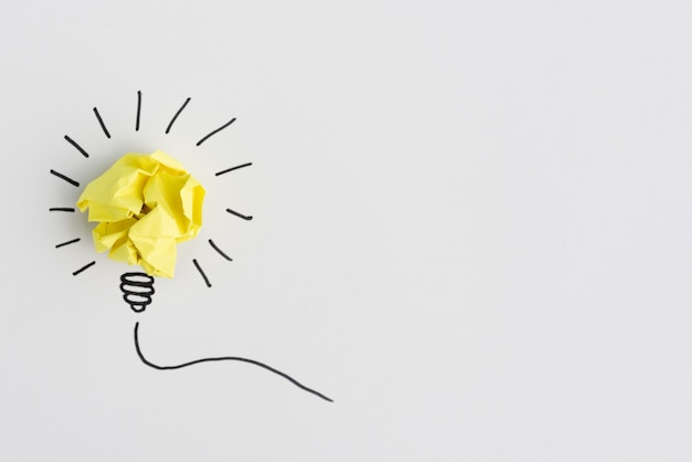 Idéia criativa lâmpada de papel amassado amarelo sobre fundo branco