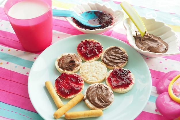 Ideia de arte alimentar. trigo redondo pães com geléia e pasta de chocolate em forma de uma flor em um prato azul. leite e um brinquedo.