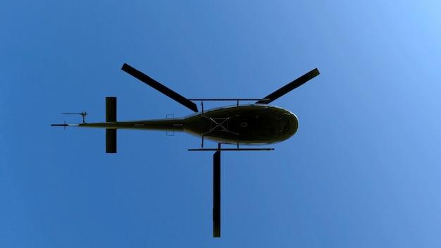 Ideia de baixo ângulo de voar o helicóptero preto do metal no céu azul.