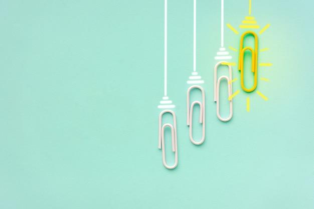 Ideia de clipe de papel conceito de sucesso ótimas ideias criativas clipe de papel de lâmpada incandescente em azul transparente