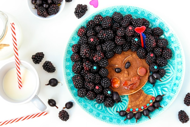 Ideia de comida engraçada para crianças menina negra comestível, rosto de panqueca, groselha e amora, arte culinária, vista de cima