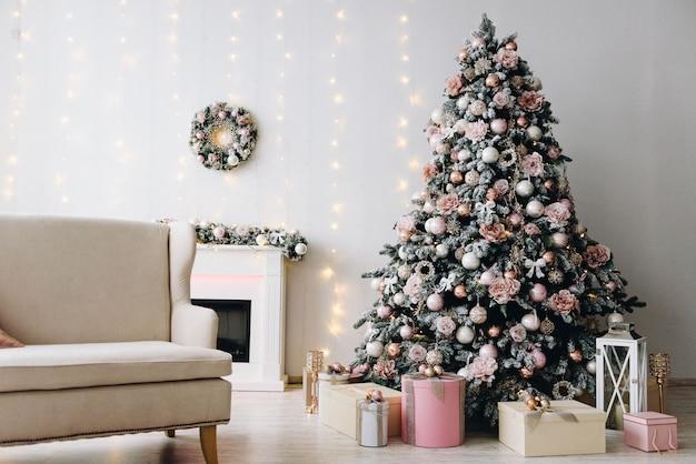 Idéia de design de interiores de natal com uma linda árvore de natal, luzes e uma lareira