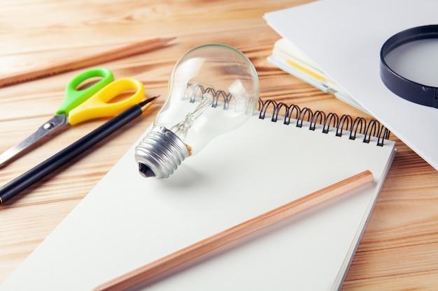 Ideia de estudo de conceito. lupa, bloco de notas, lâmpada e caneta na área de trabalho