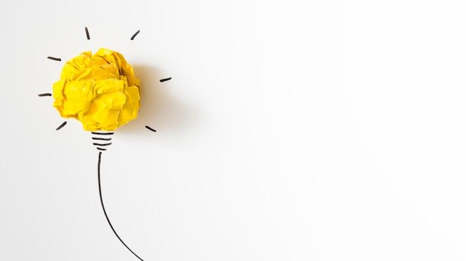 Idéia de lâmpada de papel amarelo amassado iluminada em fundo branco